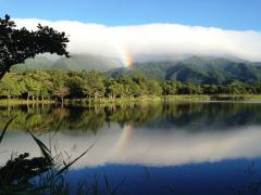 A rainbow arch reflecting in a Hokkaido lake
