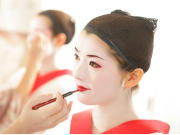 Putting on maiko white make up and lipstick