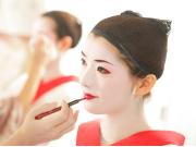 Putting on maiko white make up and lipstick