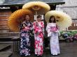 3 women wearing yukata, holding Japanese umbrellas