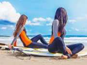 Surfer Girls Relaxing on Beach with Surfboards (Edited)