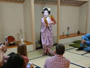 people watching maiko perform in a tatami room