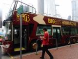 オープントップバスと赤い制服のスタッフ